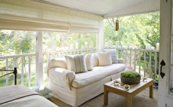 A verandah or shaded porch of a house in the woods, with cream sofa and candles along the balustrade.
